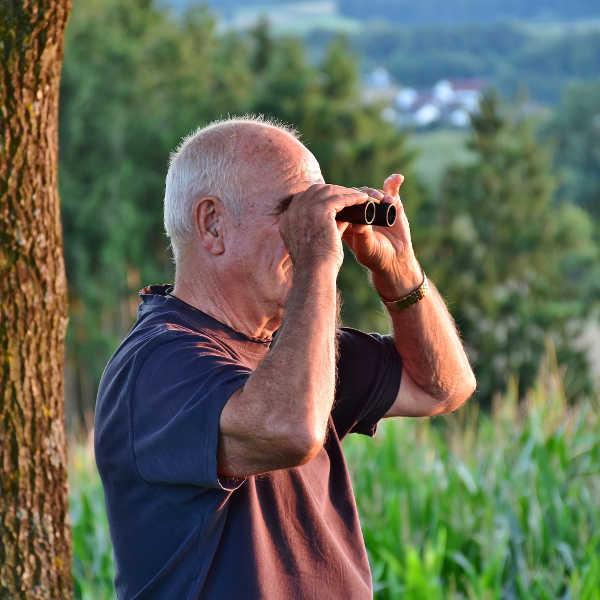 Mann-Ornithologe-mit-Fernglas-beobachtet-Vögel