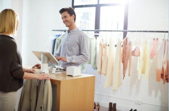 Eine Frau steht im Modehandel an der Kasse