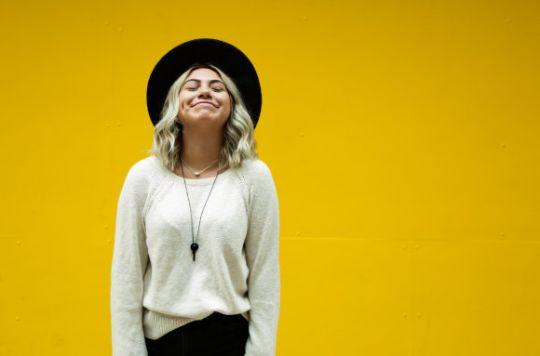 Glückliche Frau vor einer gelben Wand
