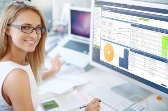 Frau sitzt am Bildschirm und arbeitet in der Warenwirtschaft