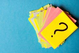 Stapel farbiger Karteikarten mit Fragezeichen auf der obersten Karte als Symbol für Fragen von Eltern