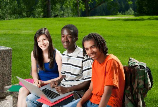 Drei Schüler der Oberstufe lernen im Park und bereiten sich während den Ferien auf die Prüfung vor