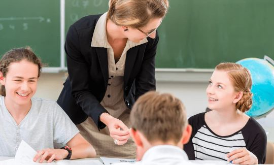 Lehrkraft im Lernforum gibt Schülern der Mittelstufe Nachhilfe nach dem individuellen Förderkonzept in der Minigruppe