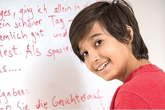Schüler der Mittelstufe zeigt seinen Deutsch-Aufschrieb an einem Whiteboard während einer Nachhifestunde