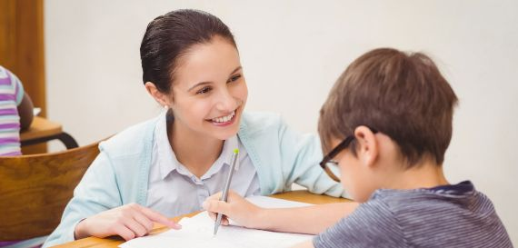 Eine junge Lerntherapeutin motiviert ein Kind mit Feingefühl in der Einzeltherapie
