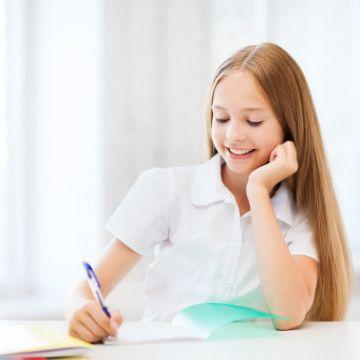 Junge Schülerin schreibt im Nachhilfe-Unterricht und nutzt den Mitschrieb für Prüfungen und Klassenarbeiten