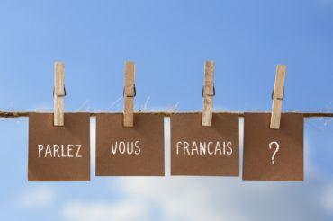 """Wäscheleine und Wäscheklammern mit vier Schildern und den Worten """"Sprechen Sie Französisch?"""""""