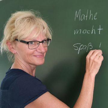 """Erfahrene Lehrkraft schreibt """"Mathe macht Spaß"""" auf die Tafel und hebt die individuelle Förderung hervor"""