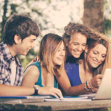 Gruppe von vier gut gelaunten Oberstufenschüler blicken gemeinsam auf eine Aufgabe während eines Intensivkurses