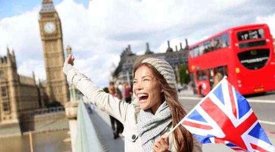 Abitur-Absolventin steht in London vor dem Big Ben mit einer UK-Flagge in der Hand und freut sich über ihr gutes Englisch