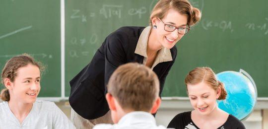 Lehrkraft im Lernforum unterrichtet drei Schüler in Mathe nach dem Lernforum-Förderkonzept