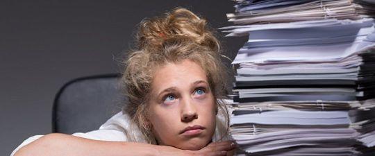 Schülerin der Oberstufe mit großem Stapel von Schulaufgaben neben sich und schaut frustriert in die Luft