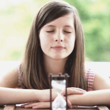 Schülerin der Mittelstufe meditiert mit geschlossenen Augen zur Entsprannung und Konzentration