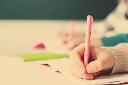 Die Hände von zwei Schülern schreiben fleißig und symbolisieren das intensive Lernen auf eine Abschlussprüfung