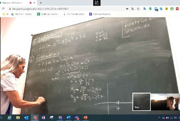 Eine Lehrkraft erklärt ihren Schülern aus der Oberstufe eine Matheaufgabe an der Tafel während eines Online-Unterrichts