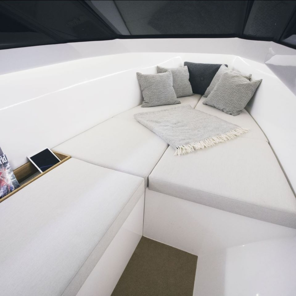 spacious double bed with extra seat area covering the toilet